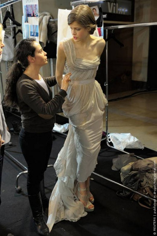 Swiss model Julia Saner waits as an assistant adjusts a creation backstage before Lebanese designer Elie Saab fashion show during the Haute Couture fashion week in Paris