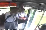 ドアの空いた走行中バスから飛び降りる少年