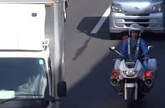 白バイに誘導されながらも携帯の通話を止めない運転手