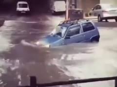 冠水した道路を渡ろうとする乗用車、このまま水没か…