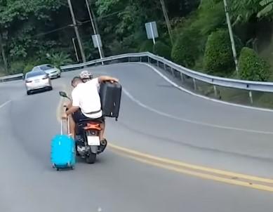 スーツケースを無茶な方法で運ぶ二人乗りバイク