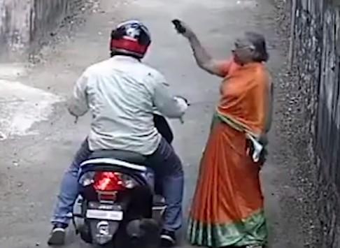 女性に道を尋ねる男性、金の装飾品を奪い去る